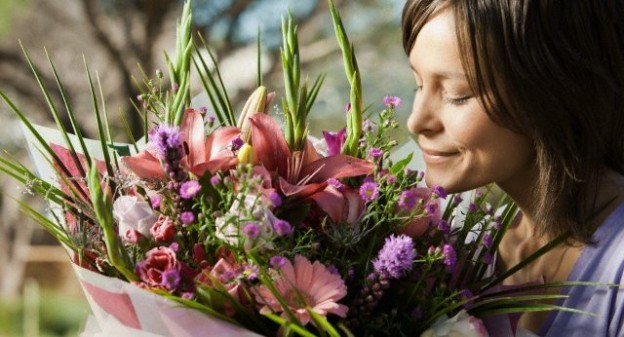 Young woman smelling a bouquet of flowers