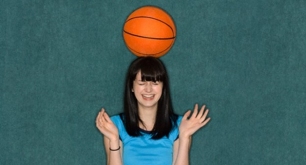 Young Woman with Basketball on Head